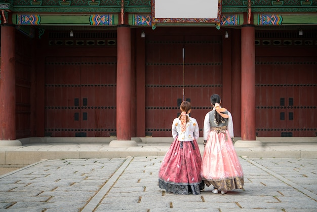 Two korean women wear hanbok korea's tradition dress to visit gyeongbokgung palace in seoul,  south korea. tourism, summer holiday, or sightseeing seoul landmark concept