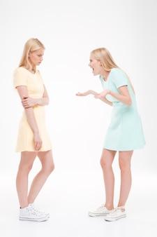 主張する2人の女性。白い壁に隔離。