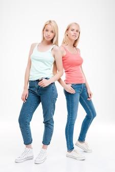 두 숙녀는 티셔츠와 청바지 포즈를 입고. 흰 벽 위에 절연. 앞을보고
