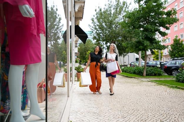 Due signore che si divertono a fare shopping, portano borse, camminano fuori dai negozi e fissano le finestre. lunghezza intera. concetto di acquisto di finestre