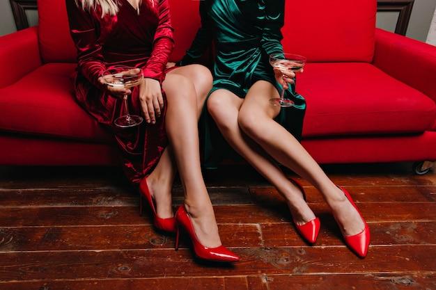 ソファに座っている赤い靴の2人の女性。ソファでポーズをとってワインを飲む華やかな女友達。