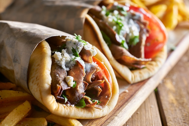 Two lamb gyros with feta cheese and tzatziki sauce