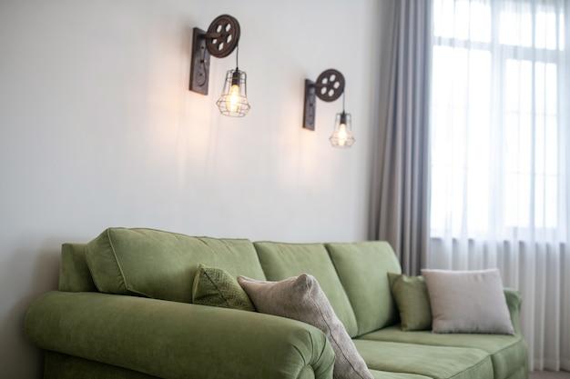 壁に掛かっている2つのランプとリビングルームに立っている柔らかいクッション付きの快適なオリーブグリーンのソファ