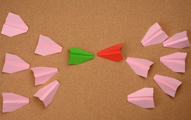 Two large groups of paper airplanes on a brown background. conflict of interest, quarrel and confrontation concept