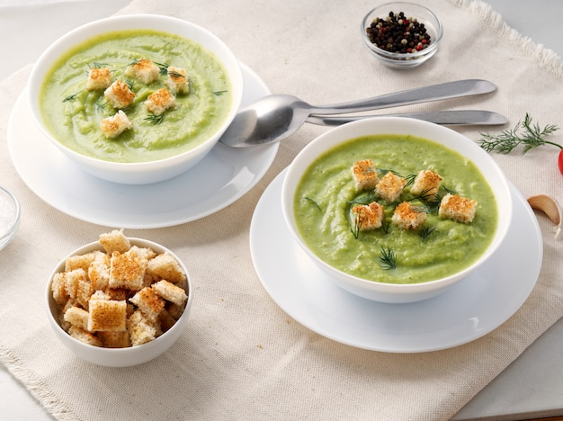 Two large white bowl with vegetable green cream soup of broccoli, zucchini