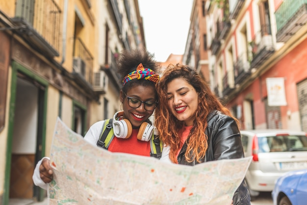 Two latin teenage girls using a map and traveling together.