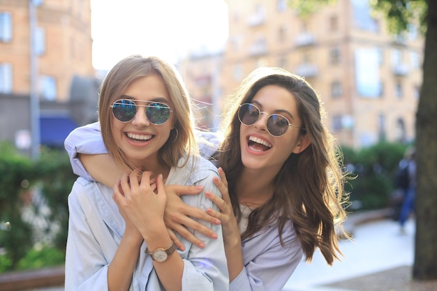 一緒に週末を楽しんで、街の背景で自分撮りを作っている2人の笑っている友人。