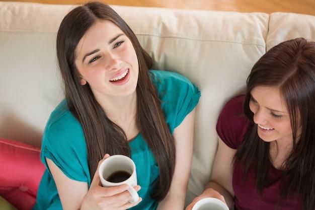 ソファにコーヒーを持っている2人の笑っている友人