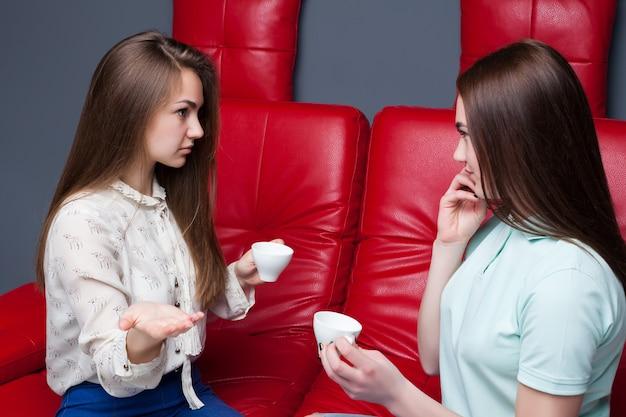 Две смеющиеся подруги пьют кофе