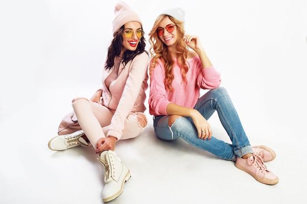2人の笑っている女の子、白い背景の上のスタジオでポーズをとる親友。トレンディなピンクの冬服。