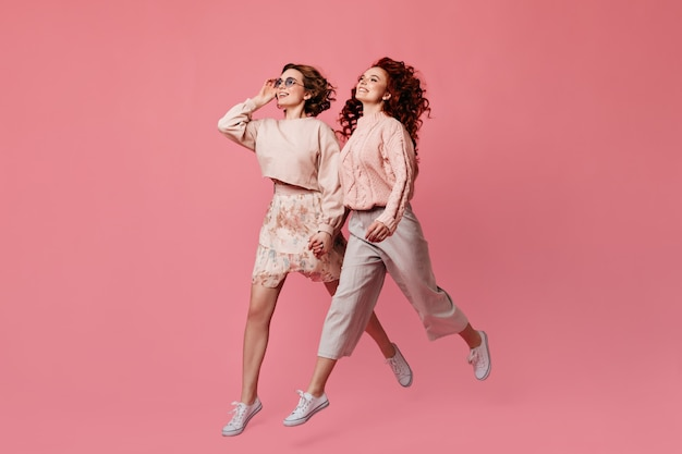 Two laughing girls holding hands. studio shot of female friends running on pink background.