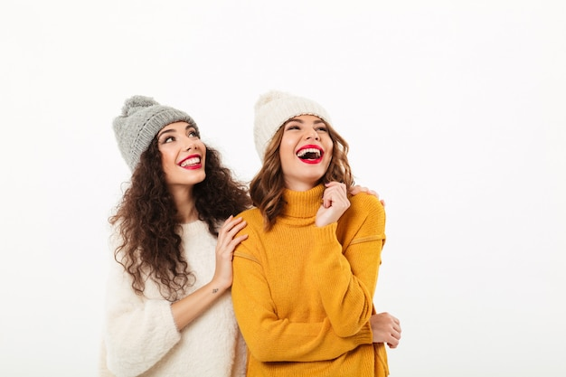 Two laughing girls in sweaters and hats standing together while looking up over white wall
