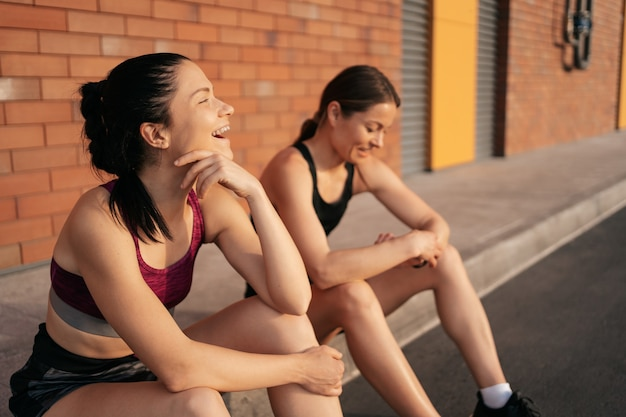 都市のトレーニングの前に2人の笑う女性。走ったり、通りに座ったりする準備をしている女の子。