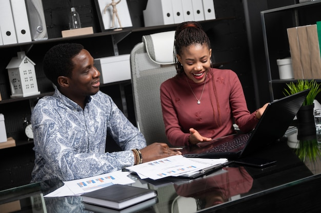 Two laughing young black people have fun discussing their business sitting at desk in office