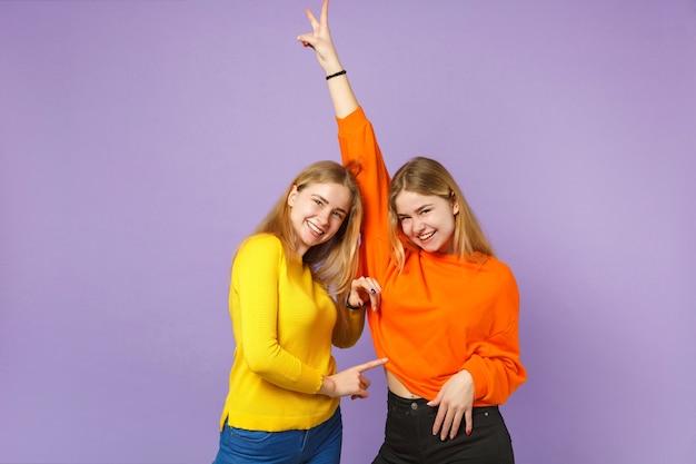 파스텔 바이올렛 파란색 벽에 고립 된 승리 기호를 보여주는 화려한 옷을 입고 두 웃는 젊은 금발 쌍둥이 자매 여자. 사람들이 가족 라이프 스타일 개념.