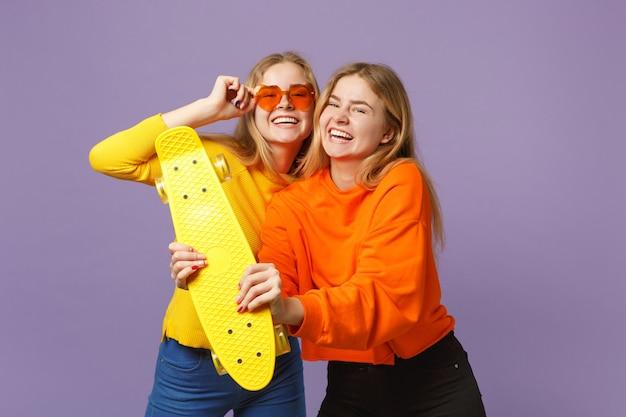 鮮やかな服を着た2人の笑う若い金髪の双子の姉妹の女の子、ハートの眼鏡はパステルバイオレットブルーの壁に分離された黄色のスケートボードを保持します。人々の家族のライフスタイルの概念。