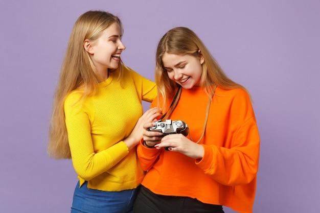 Две смеющиеся молодые блондинки сестры-близнецы девушки в яркой красочной одежде держат ретро-винтажную фотокамеру, изолированную на фиолетово-синей стене. концепция семейного образа жизни людей.