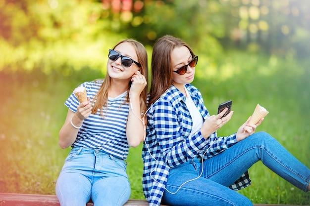 2人の笑う若い女性の女の子が夏の公園でアイスクリームを食べて音楽を聴きます。全国的なアイスクリームの日です。楽しい休暇、友達とのコミュニケーション。
