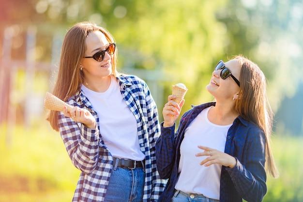 두 명의 웃고 있는 젊은 여성 소녀들이 국가 아이스크림의 날인 여름 공원에서 아이스크림을 먹습니다. 즐거운 휴가, 친구와의 소통.