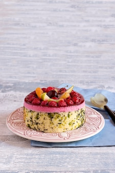 Two-layered pie with jellied fruit and berries on plate