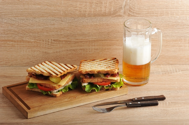 Two layered sandwich with bacon and chicken breast on a wooden board