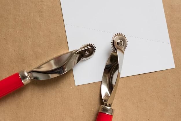 白い穴あき紙に2つの革の裁縫道具。閉じる