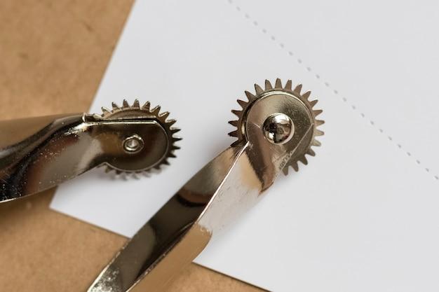 白い穴あき紙に2つの革の裁縫道具。コピースペース