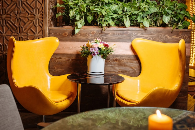 Two leather yellow armchairs and coffee table at the restaurant