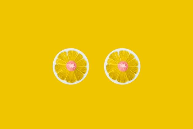 노란색 배경에 두 개의 레몬 조각입니다. 유방암 개념