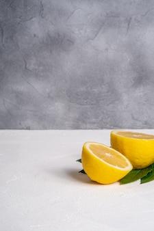 두 레몬 조각, 흰색 콘크리트 배경에 녹색 잎 열대 감귤류, 각도보기 복사 공간
