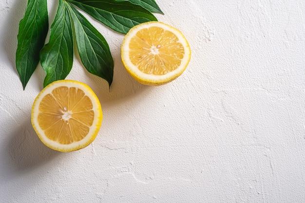 두 레몬 조각, 흰색 콘크리트 배경에 녹색 잎 열대 감귤류, 상위 뷰 복사 공간