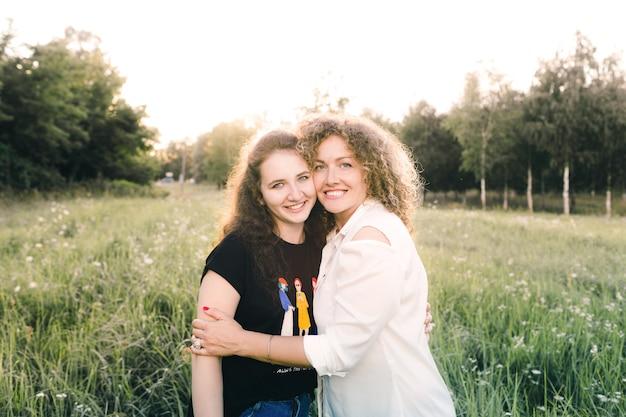 두 레즈비언 소녀는 공원의 잔디에 앉아 서로 포옹하고 있습니다. 동성애. lgbt 사람들