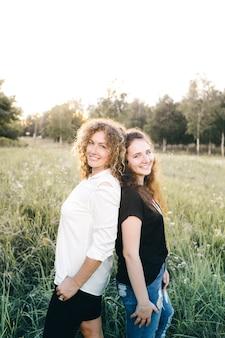 두 레즈비언 소녀가 공원의 잔디 위에 서로 등을 대고 서 있습니다. 동성애. lgbt 사람들