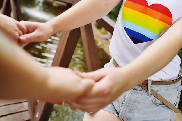 Two lesbian girls holding hands gently.