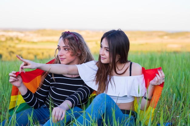 Two lesbian girls lying on the grass with the gay pride flag