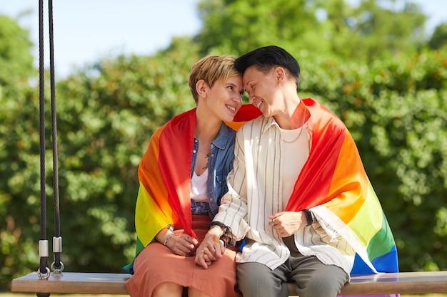 ブランコに座ってレズビアンの旗で覆い、屋外で抱きしめる2人のレズビアン