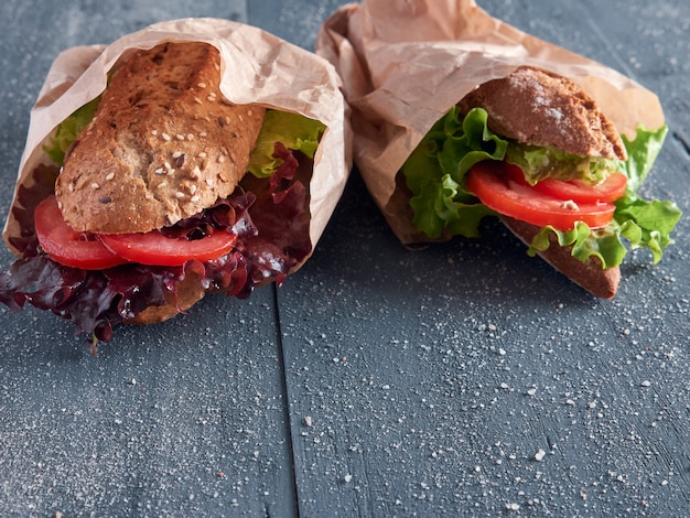 Two lettuce and tomato baguettes on paper bags, isolated on a dark wooden background