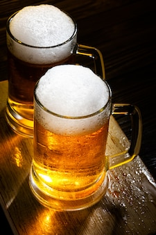 Two light beer mugs with foam on table