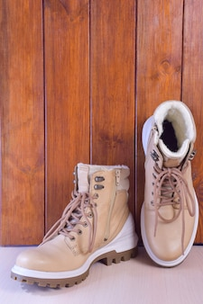 Two light winter or autumn boots on a brown wooden background. the right one is upright.