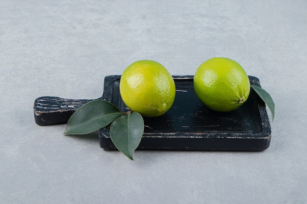 Two lime fruits with leaves on cutting board.