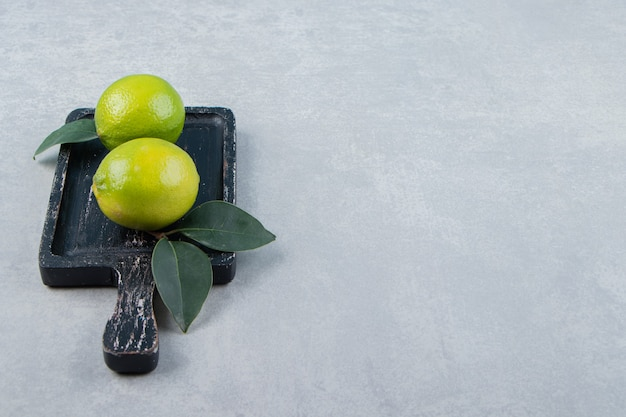 Two lime fruits with leaves on cutting board