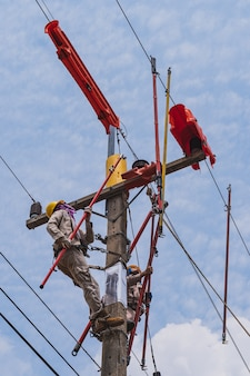 Two linesmen use insulated equipment to repair and maintain high-voltage distribution systems.