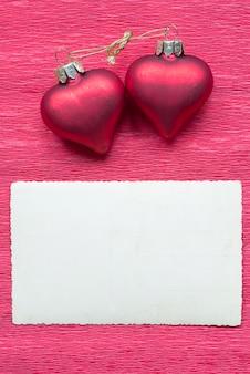 赤い紙の背景にヴィンテージはがきと2つのリンクされたハート
