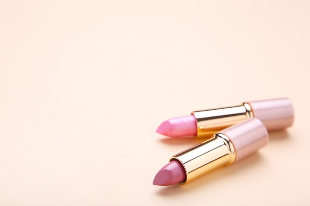 Two lipsticks on beige background, close up