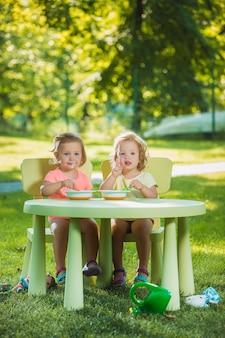2人の小さな2歳の女の子がテーブルに座って、緑の芝生に対して一緒に食べる