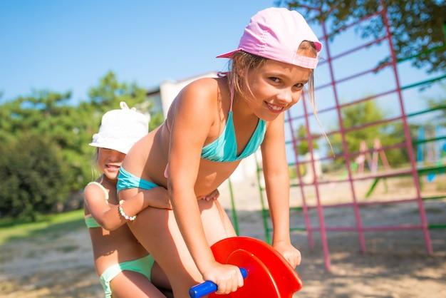 Две очаровательные сестренки-девочки играют друг с другом на детской площадке у моря в солнечный теплый летний день во время отпуска. концепция детских игр на улице