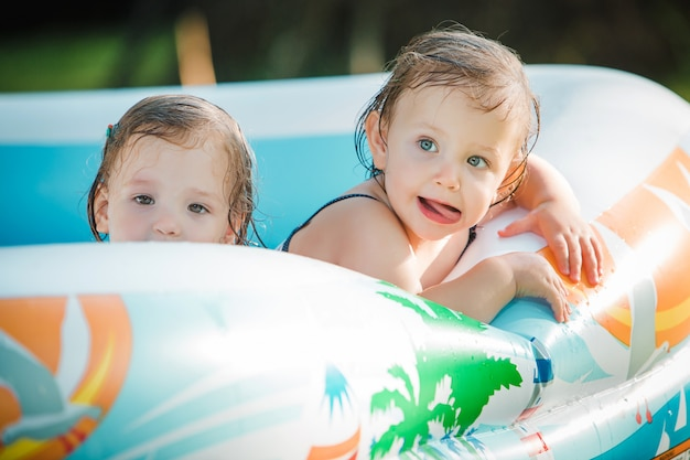The two little baby girls playing with toys in inflatable pool in the summer sunny day