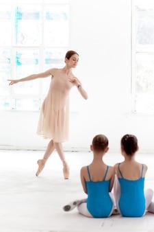 댄스 스튜디오에서 개인 발레 선생님과 함께 춤추는 두 명의 작은 발레리나