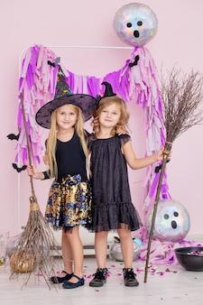 ファッショナブルなハロウィーンのカーニバル魔女の衣装を着た2人の小さな美しいかわいい子供たちの女の子