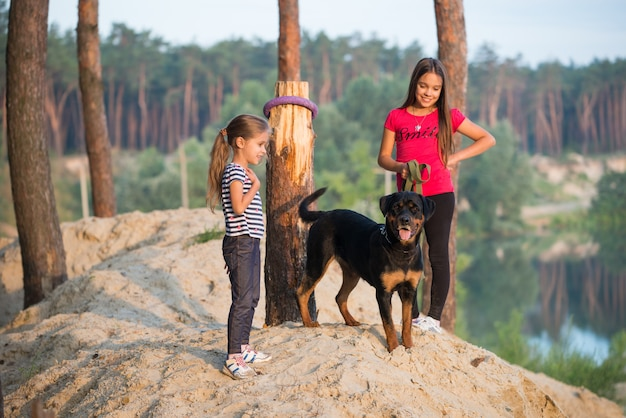 Two little beautiful cute girl and a big adult rottweiler dog, sitting on the edge of a sandy cliff hugging and enjoying a warm summer morning in a dense spruce forest